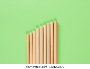 Bamboo straws close to each other on a green flat lay. Also a growth chart