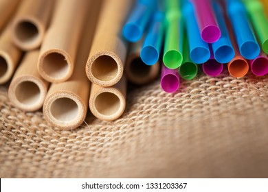 Bamboo straws and colorful plastic straws lying next to each other on a natural fabric