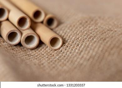 Bamboo straws lying diagonally on a natural-looking brown fabric