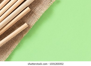 Bamboo straws lying on a brown natural-looking fabric on a pastel green flat lay