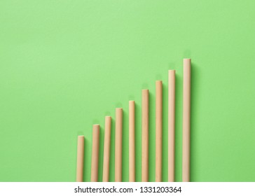 Bamboo straws with spaces between them on a green flat lay. Also a growth chart