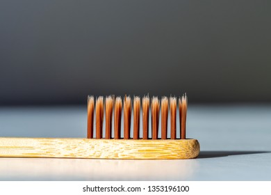 Bamboo tooth brush on white surface under bright sun light