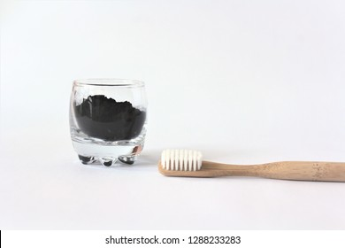 bamboo toothbrush and activated charcoal into glass isolated on white background