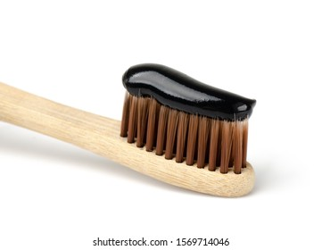 Bamboo toothbrush with black charcoal toothpaste. Close up of black toothpaste on toothbrush.