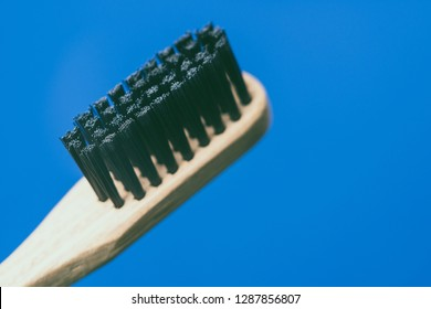 Bamboo toothbrush, closeup view, isolated on blue background
