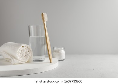 Bamboo toothbrush, glass of water, white a cotton towel and powder for brushing your teeth in jar. light gray concrete surface, gray backdrop. Biodegradable personal care products. No plastic concept. - Shutterstock ID 1639933630