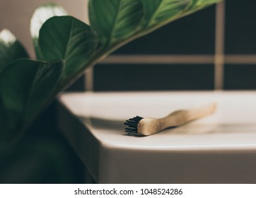 Bamboo toothbrush sitting in bathroom with green flower