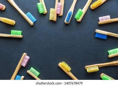 bamboo toothbrushes in different colours on dark rough background. plastic-free concept