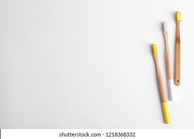 Bamboo toothbrushes on white background, top view. Space for text