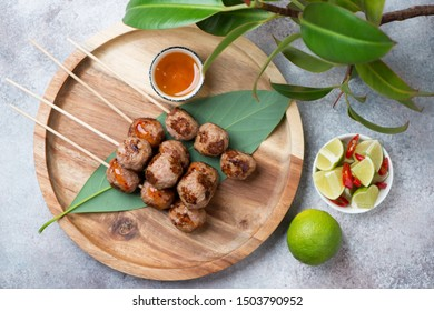 Bamboo tray with vietnamese nem nuong or fried pork meatballs on skewers, top view on a beige stone background