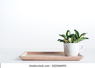 Bamboo tray with white coffee mug and yellow-green leaves