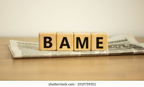 BAME symbol. Abbreviation BAME, black, asian and minority ethnic on wooden cubes on newspaper. Beautiful white background. Copy space. Business and BAME, black, asian and minority ethnic concept.
