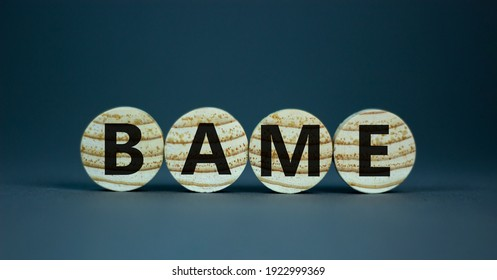 BAME symbol. Abbreviation BAME, black, asian and minority ethnic on wooden circles. Beautiful grey background. Copy space. Business and BAME, black, asian and minority ethnic concept.