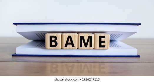BAME symbol. Abbreviation BAME, black, asian and minority ethnic on wooden cubes in book. Beautiful white background. Copy space. Business and BAME, black, asian and minority ethnic concept.