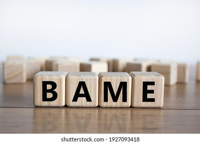 BAME symbol. Abbreviation BAME, black, asian and minority ethnic on wooden cubes. Beautiful wooden table, white background. Copy space. Business and BAME, black, asian and minority ethnic concept.