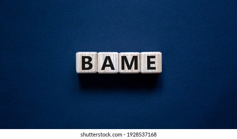 BAME symbol. Abbreviation BAME, black, asian and minority ethnic on wooden cubes. Beautiful grey background. Copy space. Business and BAME, black, asian and minority ethnic concept.