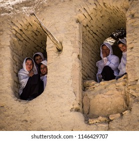 Bamiyan, Afghanistan, May 2004: Hazara women watch the world got by from the ruins of a buidling in Bamyan, Afghanistan