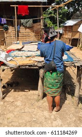 Ban Houay Phod, Laos-October 8, 2015: The Akha Ya-Er hill tribe are an ethnic minority living in the area between E.Myanmar-N.Thailand-W.Laos-S.China. Woman setting food on trays to dry under the sun.