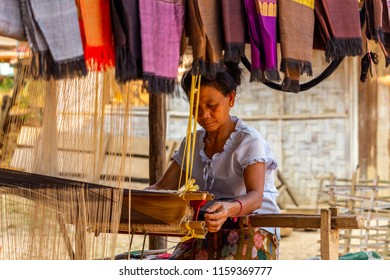 Ban Na, Laos - April 10, 2018: Ethnic minority sewer creating tribal scarfs in a remote village of northern Laos. Credit: Dino Geromella/Shutterstock