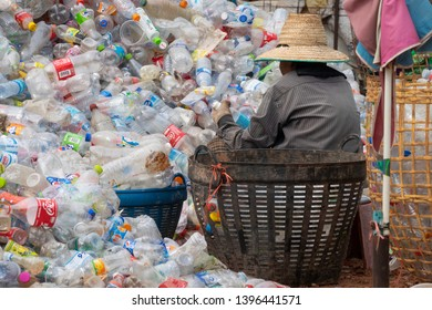 Ban Nam Chum, Udon Thani, Thailand - May 12, 2019: Female workers of a plastic collection factory prepare manually plastic bottles for proper recycling.