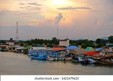 Ban Pak Nam Krasae, Klaeng district, Rayong Province, THAILAND - JUN. 3, 2019 : Local fishing pier with fishing boats and beautiful sunset sky.
