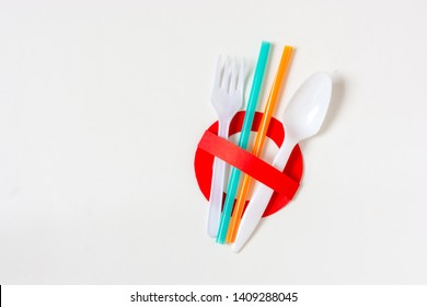 Ban single use plastic. A creative artwork of stop sign over colorful plastic straws, fork, spoon, on white background. Pollution/environmental concept. Say no to plastic. Save the world.