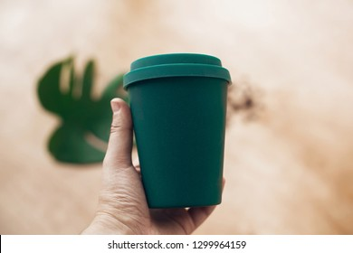 Ban single use plastic. Hand holding eco reusable coffee cup on wooden background. Coffee cup from bamboo fiber, zero waste concept.  Take away coffee in your cup. Sustainable lifestyle