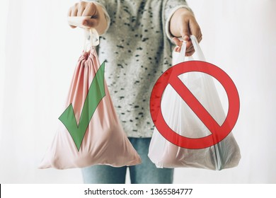 Ban single use plastic, stop sign. Choose plastic free. Zero Waste shopping concept. Woman holding in one hand groceries in reusable eco bag and in other vegetables in plastic polyethylene bag
