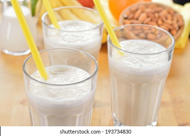 Banana and almond milk smoothie in a glass on a kitchen table. Summer drink made of banana, almond milk