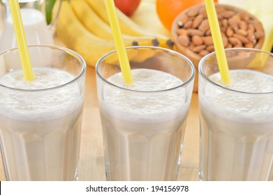 Banana and almond milk smoothie in a glass on a kitchen table. Summer drink made of banana, almond milk and few dactyl.