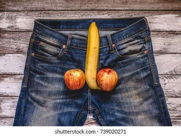 banana and apple out of mens jeans like mens penis. potency concept