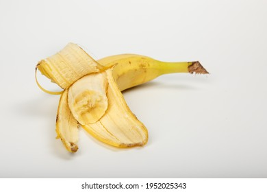 Banana bitten. A peeled and bitten banana in a peel on a white background. Old one peeled banana. Tropical yellow fruit. Selective focus. Bitten Banana.