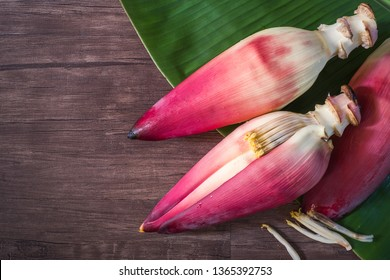 Banana blossom with banana leaves placed on an old wooden plates.top view.Banana blossom helps to nourish the blood.