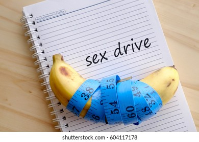 Banana with blue measuring tape, notebook with text SEX DRIVE. Men's health concept.