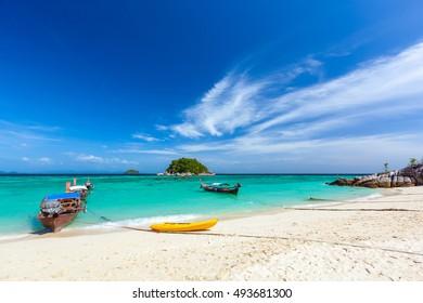 Banana boat and fishing boats moor by the clean sandy beach of Ko Lipe Island