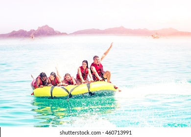 Banana boat fun for group of friends on summer holiday - Active teenagers having thrilling experience at riding on island sports attraction on sunny vacation day - Sun halo filter with hazy background