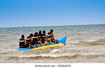 Banana boat in sea. Group of young people riding banana boat