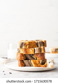 Banana bread (banana cake) with chocolate chips and milk. Stack of pieces of cake. Moist and delicious homemade dessert, tasty snack, morning breakfast concept. Copy space, white concrete background.