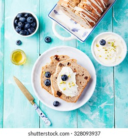 Banana bread with cream cheese frosting, honey, fresh berries blueberries on a turquoise wooden background