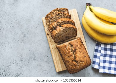 Banana bread loaf with almond nuts sliced on grey concrete background. Table top view and copy space