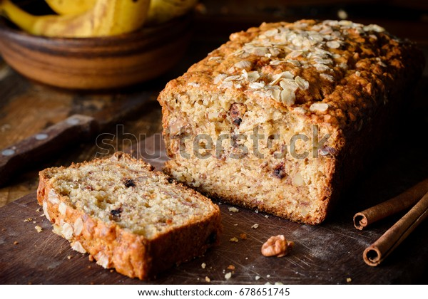 Banana bread loaf with walnuts and cinnamon on wooden board. Closeup view