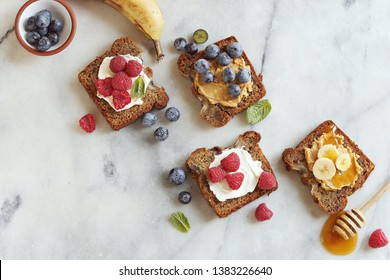 Banana bread sandwiches with peanut butter und fresh berries. Healthy gluten free snack for paleo, clean eating, super food and healthy eating contepts. Overhead view