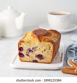 Banana bread, sliced cake with banana and blueberries. Morning breakfast with tea on light gray cincrete background
