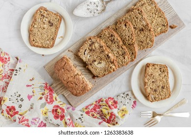 banana bread slices on a wooden board on a white table