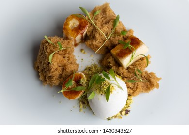 Banana and caramel deconstructed cake with a lemon sorbet resting on a pistachio crumb base. Presented on a white plate on a dark table. Multiple shots taken from different angles.