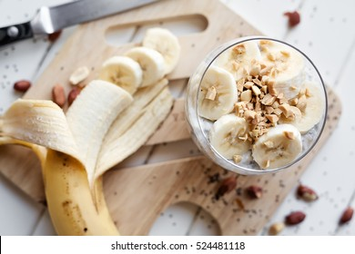 Banana chia yogurt pudding decorated with ripe sliced banana and peanuts