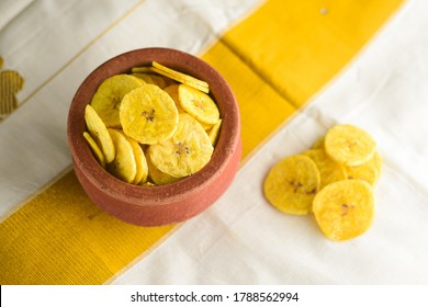 Banana chips or Kaya Varuthathu Kerala fried snacks in terracotta or clay pot on white Kerala sari background popular in South India Tamil Nadu, Top view of Indian tea time food fried in coconut oil.