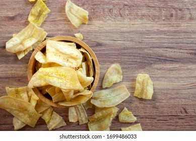 banana chips in wooden bowl on wooden background.