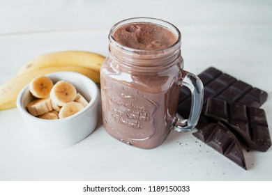 Banana and chocolate smoothie in the glass jar milkshakes, natural and organic drink