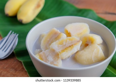 Banana in coconut milk on wooden table
